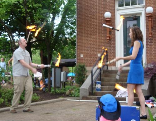 Jugglers throw fire.