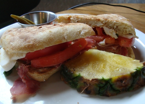 Sonoma sandwich, made with proscuitto, mozzarella, tomato, basil, balsamic vinegar and olive oil on ciabatta bread. Came with a slice of pineapple and a pickled okra.